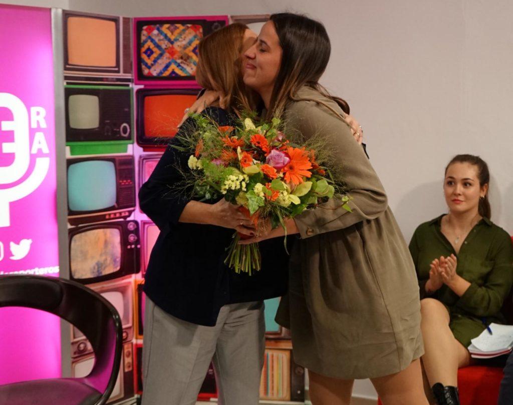 La periodista Ana Gomar hace entrega de un ramo de flores a Eva Casanueva